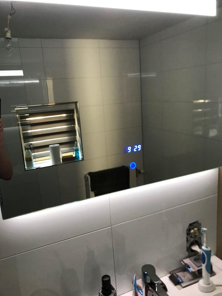 Spiegel met led verlichting en klok op witte tegel