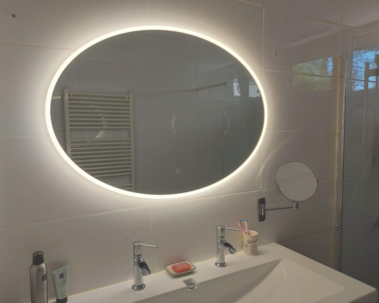 Grote ovalen spiegel met verlichting op witte tegel met aparte scheerspiegel